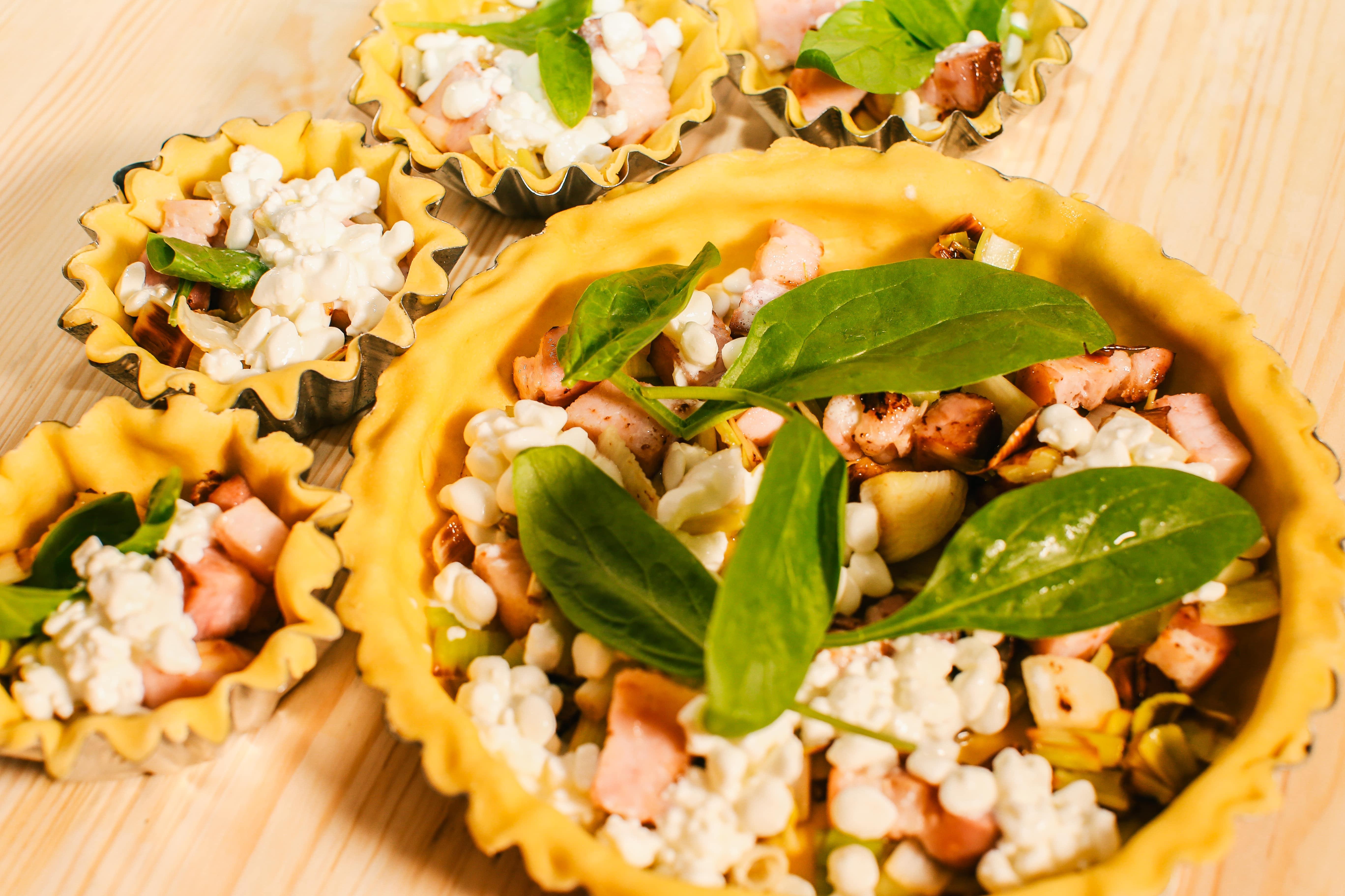 Викласти на тісто шинку з цибулею, залити молочно яєчною сумішшю та додати зернистий сир і шпинат.